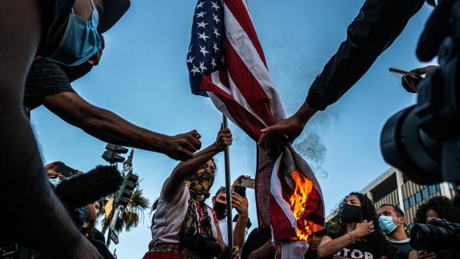 Varias personas queman una bandera de EE UU en Los Ángeles durante las protestas.