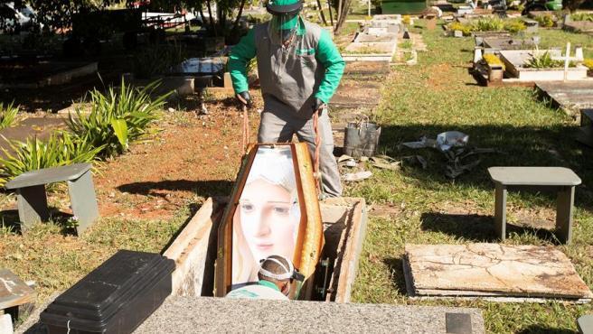 Trabajadores del cementerio Campo de Esperanza, en Brasilia (Brasil), entierran a un fallecido por COVID-19.