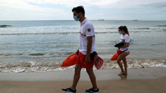 Dos socorristas con mascarilla en la playa.