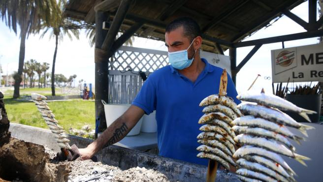MLG 20-05-2020.-Un espetero prepara sardinas en las playas de Pedregalejo.-ÁLEX ZEA.