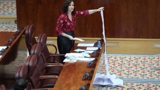 La presidenta de la Comunidad de Madrid, Isabel Díaz Ayuso, muestra una lista de residencias de mayores atendidas en la crisis del coronavirus durante un sesión plenaria en la Asamblea de Madrid