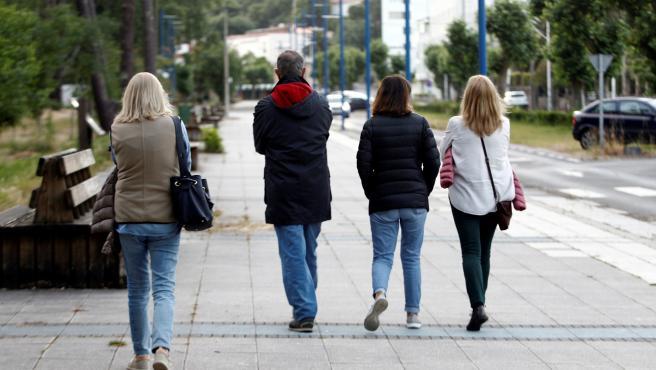 Varias personas dan un paseo en la tarde del jueves por la localidad coruñesa de Cabanas.