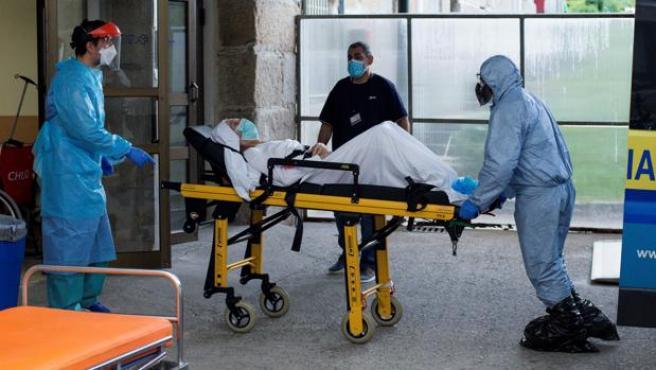 Personal sanitario traslada a un paciente con Covid-19 al Hospital de Piñor, en Ourense.
