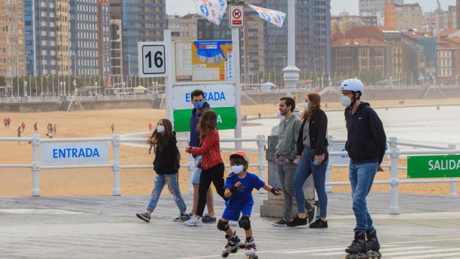 Un grupo de personas pasean por el paseo marítimo de la playa de San Lorenzo de Gijón.