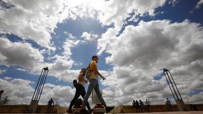 Gente protegida con mascarilla pasea junto al puente romano de Córdoba durante la fase 3 de la desescalada.