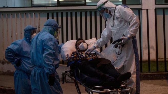 Un médico toma la temperatura a un paciente de COVID-19 a su llegada al hospital general San Juan de Dios, en Ciudad de Guatemala (Guatemala).