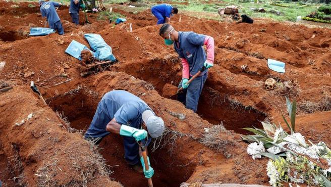 Sepultureros del cementerio de Vila Formosa, el más grande de América Latina, en Sao Paulo (Brasil), abren nuevas fosas para fallecidos por COVID-19.
