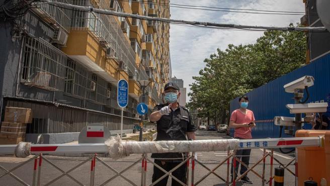 Un guardia de seguridad, en una zona residencial cercana a un mercado de Pekín, China, cerrada tras detectarse en la zona un rebrote de coronavirus.