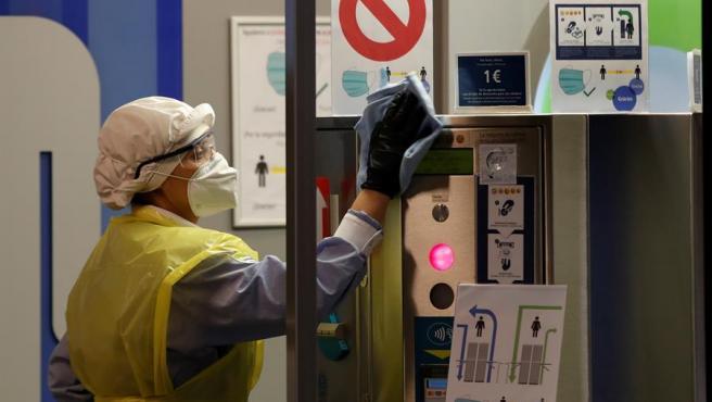 Una trabajadora con material de protección por la pandemia del coronavirus desinfecta los accesos a los servicios de la estación de Sants, en Barcelona.