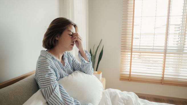 Una mujer en la cama con signos de haber dormido mal.