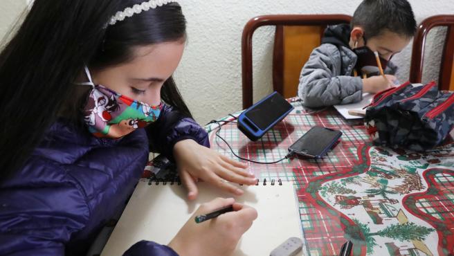 Dos niños colombianos estudian con mascarilla.