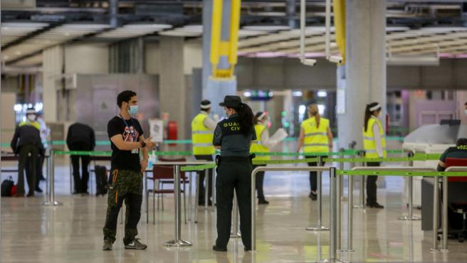 Agentes de la Guardia Civil y personal del aeropuerto de Madrid-Barajas Adolfo Suárez controlan la llegada de pasajeros el día en el que se estrena el triple control sanitario.