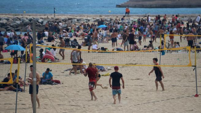 Un grupo de jóvenes jugando en la playa del Bogatell de Barcelona.
