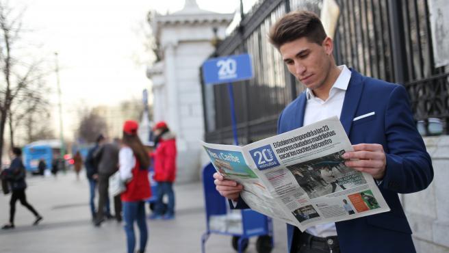 Un lector recoge un ejemplar de 20minutos.