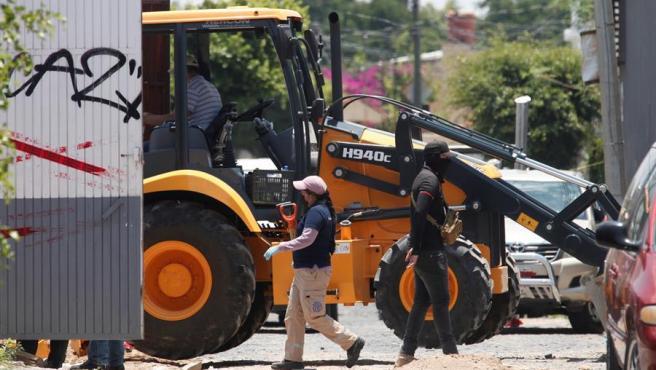 Peritos forenses y personal de la Fiscalía del Estado recaban información en una fosa clandestina en Tlaquepaque, en el estado de Jalisco (México), tras el hallazgo de al menos 75 bolsas con restos humanos.
