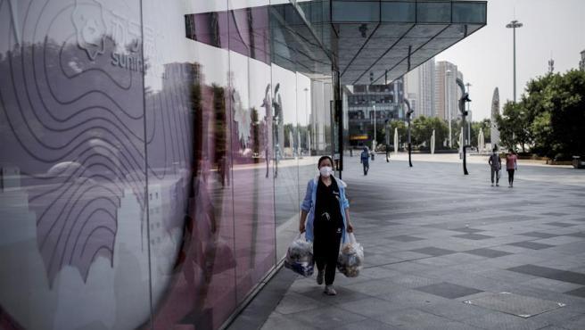 Una mujer con mascarilla por la pandemia del coronavirus, en un centro comercial de Pekín, China.