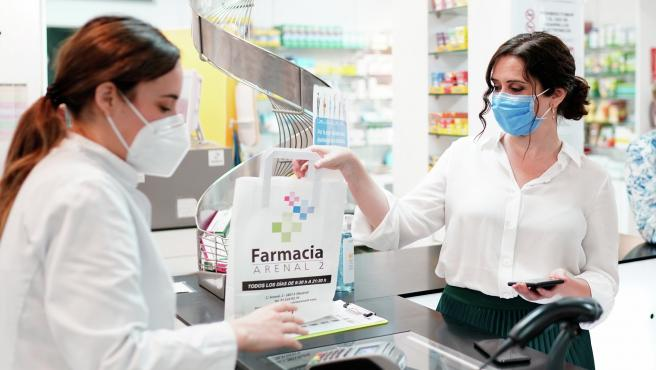 La presidenta de la Comunidad de Madrid, Isabel Díaz Ayuso, durante la visita a una oficina de farmacia para presentar la tarjeta sanitaria virtual en la región.