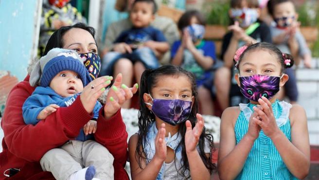 Niños con mascarillas por la pandemia del coronavirus asisten a un espectáculo de artistas callejeros en Bogotá (Colombia).
