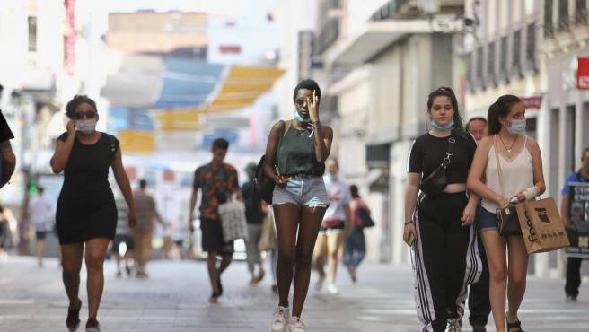 Varias personas caminan por la calle Preciados de Madrid en plena ola de calor.