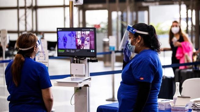Personal médico controla en una pantalla la temperatura de los pasajeros por la pandemia del coronavirus, en el aeropuerto internacional Tom Bradley, en Los Ángeles (EE UU).
