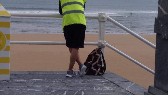 Un 'acomodador de playa' en San Lorenzo, en el primer día de este servicio de control y asesoramiento de aforos