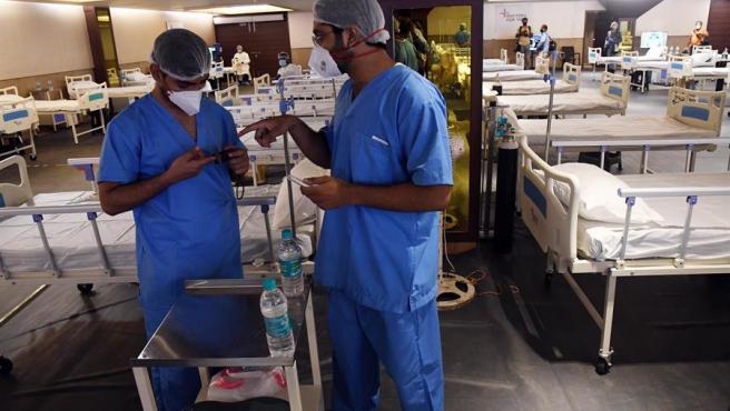 """Dos médicos en un """"hospital"""" temporal preparan camas en una sala de aislamiento para pacientes con Covid-1 (Nueva Delhi)"""
