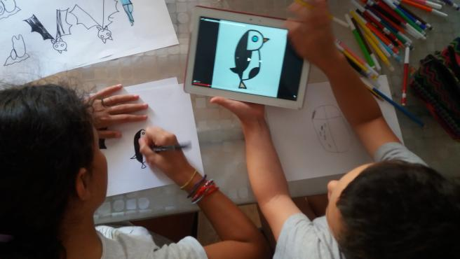 Niños dibujando letras con forma de animal.