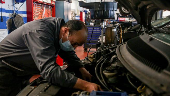 Un trabajador con mascarilla arregla un vehículo en talleres Otman, en el polígono industrial Ventorro del Cano en Alcorcón