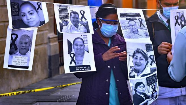 Trabajadores sanitarios muestran imágenes de colegas fallecidos por COVID-19, durante una protesta en Ciudad de México.