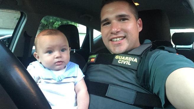 Imagen del guardia civil junto con el bebé al que salvó la vida tras reanimarle cuando había entrado en parada