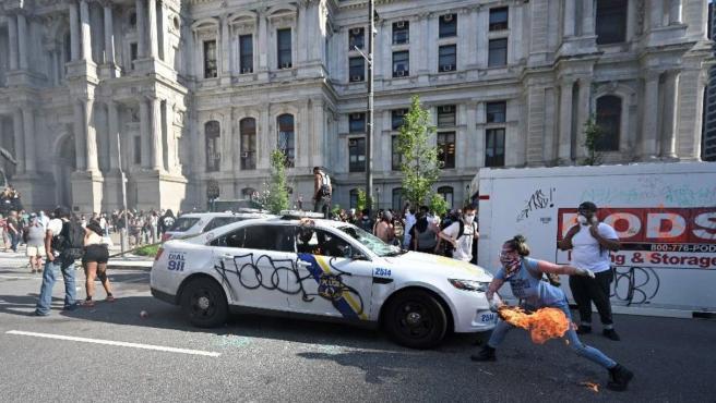 Imagen de la manifestante lanzando un objeto en llamas a un coche de la Policía.