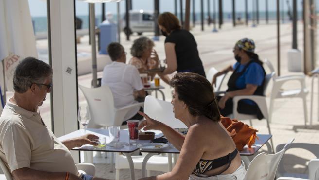Varias personas en un bar del paseo marítimo de la playa de Matalascañas en Huelva en una imagen de archivo.