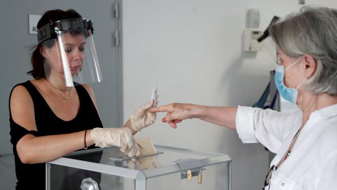 Una persona vota en Perpiñan guardando las medidas sanitarias por la pandemia del coronavirus.