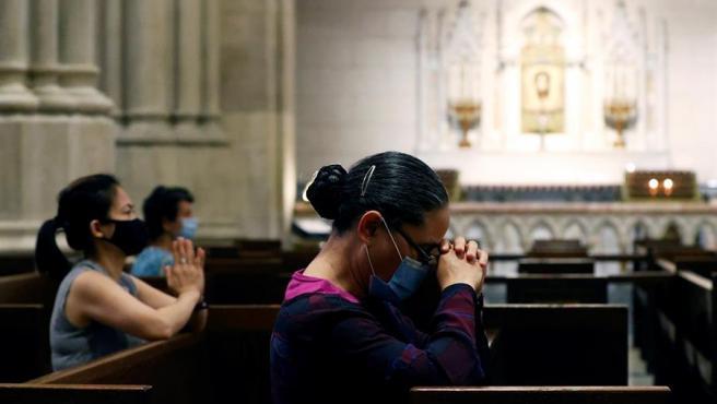 Varios fieles con mascarillas por la pandemia del coronavirus rezan en la catedral de San Patricio, en Nueva York, EE UU.