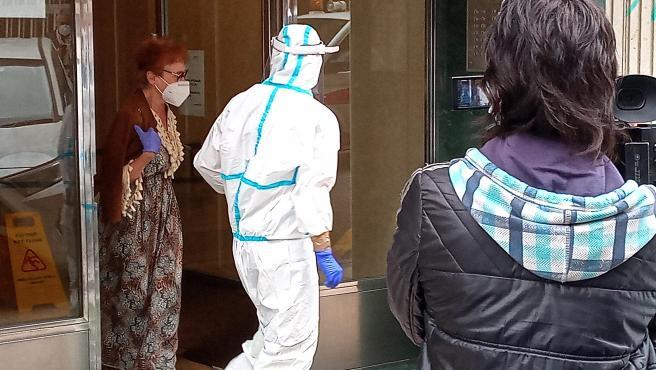 Una de las vecinas del inmueble de Santander en cuarentena que ha dado positivo en la prueba de la covid-19 es trasladada para ser examinada.