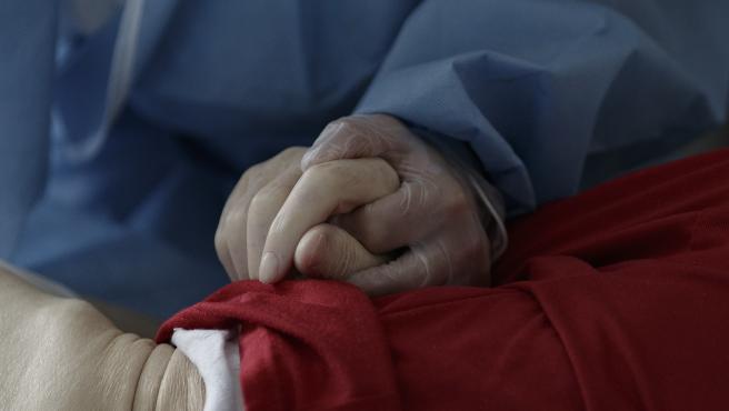 Una trabajadora sujeta la mano de un mayor en un centro