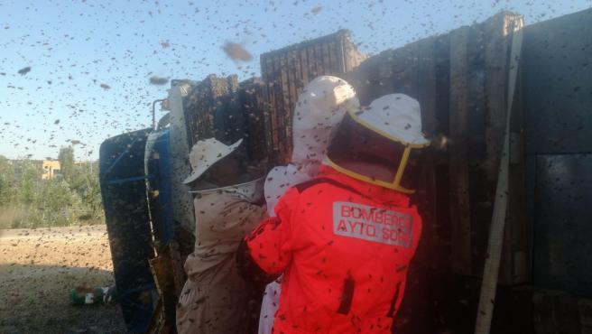 Imagen de los bomberos en la intervención para retirar los panales de abejas