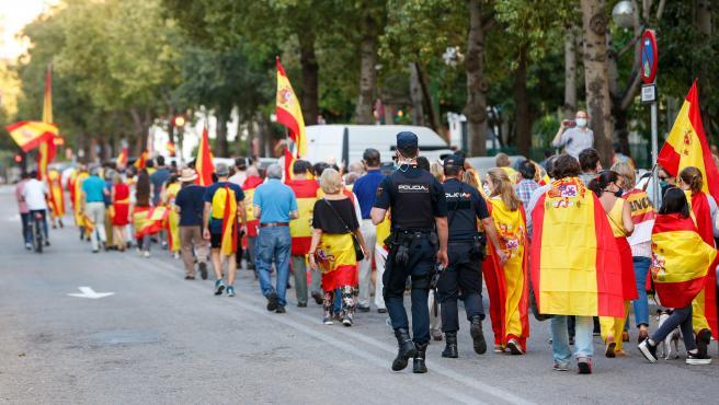 Manifestantes por el barrio del Polvenir con la bandera española en una concentración contra el Gobierno central por su gestión ante la pandemia