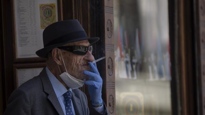 Un hombre con mascarilla y guantes fumando un cigarro durante el quinto día de la fase 2 en Sevilla (Andalucía, España), a 29 de mayo de 2020.