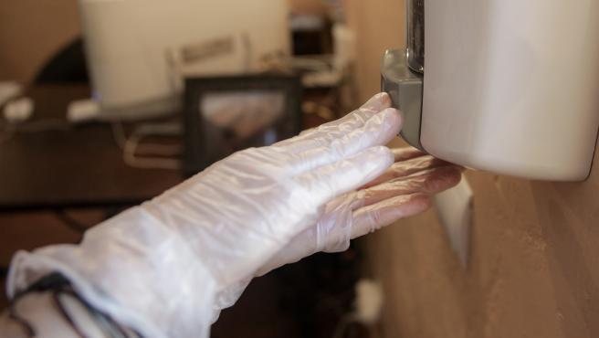 Un trabajador protegido con mascarilla coloca gel desinfectante en un dispensador para clientes
