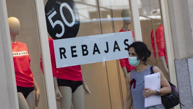 Una persona pasa al lado de un escaparate de una tienda de la capital con carteles de descuentos durante el segundo día de rebajas, en Madrid (España), a 26 de junio de 2020.