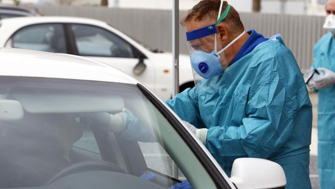 MLG 23-03-2020.-Un enfermero realiza la prueba test del PCR para detectar la infección por coronavirus enel recinto de aparcamineto del centro de salud de la barriada La Roca, en la imagen un enfermero sujeta un test de PCR.-ÁLEX ZEA.