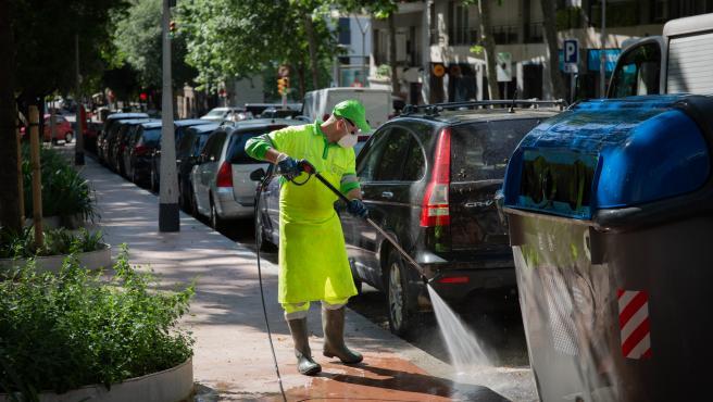 Un operario de limpieza del servicio municipal desinfecta un contenedor de basura