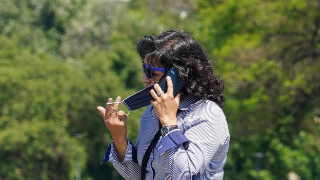 Una mujer se quita la mascarilla para hablar por teléfono mientras pasea por el puente de triana en el primer día del uso obligatorio de mascarillas por el Covid-19. Sevilla a 21 de mayo del 2020