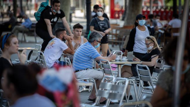Varias personas disfrutan en la terraza de un bar durante el segundo día de la reapertura al público de las terrazas al aire libre. En Barcelona, Catalunya (España) a 26 de mayo de 2020.