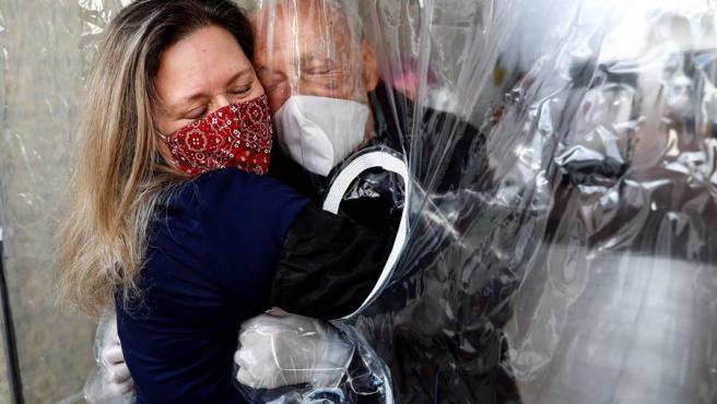 Una mujer abraza a su padre de 82 años a través de una cortina en una residencia de ancianos de Sao Paulo (Brasil), durante la pandemia del coronavirus.