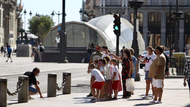 Un grupo de personas pasea por la Puerta del Sol de Madrid.