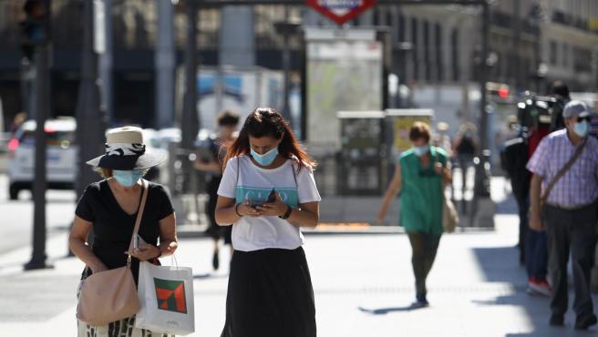 Varias personas pasean por el centro de Madrid con mascarillas.