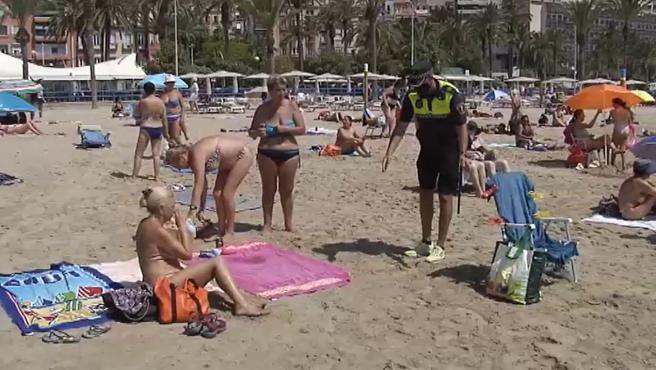 Un agente de la Policía Local da instrucciones a los bañistas.