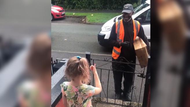 Una niña conversando con el repartidor que pasaba siempre por su calle durante la cuarentena.